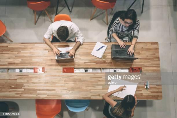 geschäftsleute, die am schreibtisch arbeiten - coworking stock-fotos und bilder