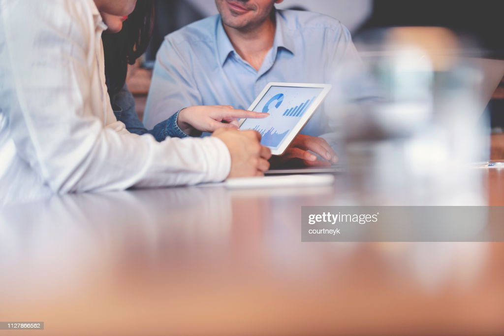Business people working on financial data on a digital tablet. : Stock Photo