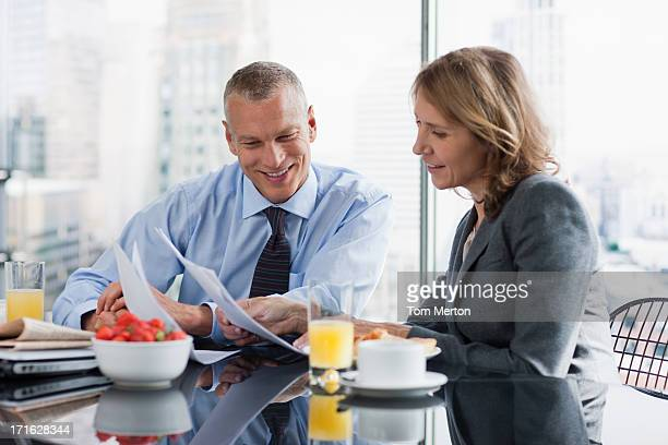 Business people working over breakfast