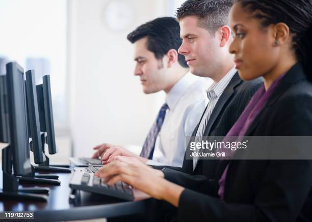 Business people working together in office on computers