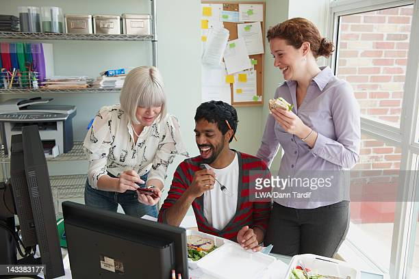 Business people working together in office over lunch