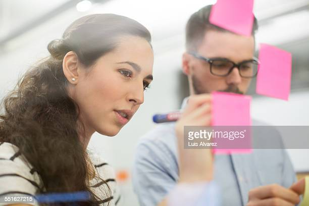 Business people writing on adhesive notes