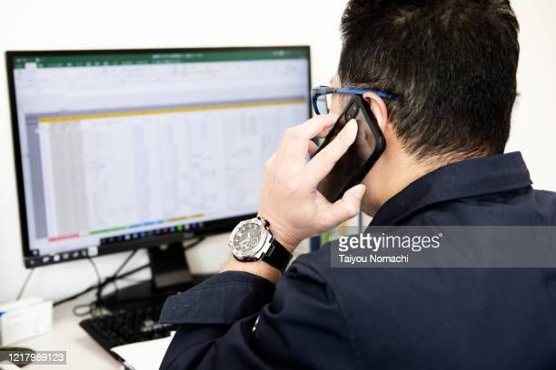 business person calling while checking data - 検査業務 開始の地 ストックフォトと画像