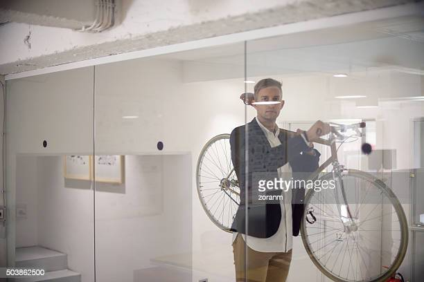 Business person carrying his bicycle