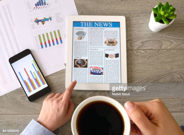 business person drinking coffee and reading news on tablet pc - the media stock photos and pictures