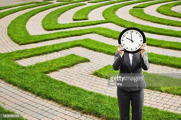 Homme d'affaires en face de temps délai, perdu dans le labyrinthe d'emploi