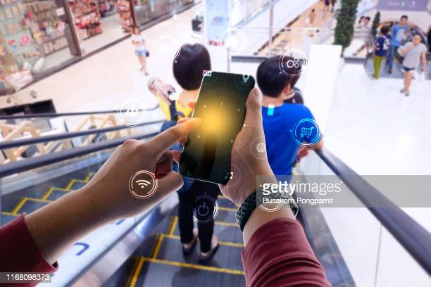 business person hand holding mobile phone with icons. concept of business and technology communication in the network. - multimedia stock pictures, royalty-free photos & images