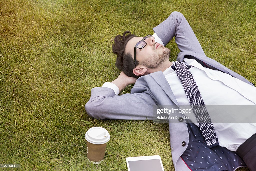 business person having break, laying in park. : Stock Photo