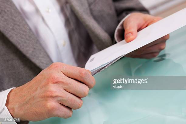 Business person opening an envelope
