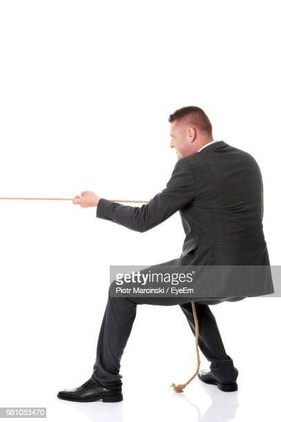 Business Person Pulling Rope While Standing On White Background