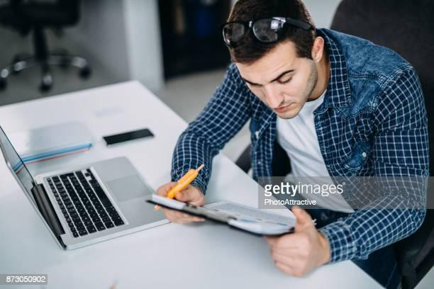 Bedrijfspersoon lezen van gegevens op papier grafieken en Computer