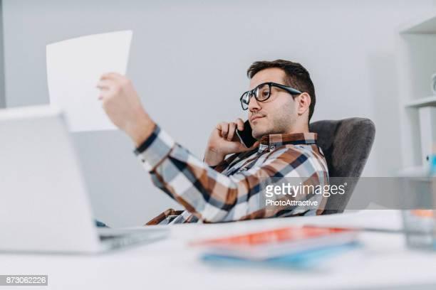 Bedrijfspersoon lezen van gegevens op papier grafieken en met behulp van slimme telefoon