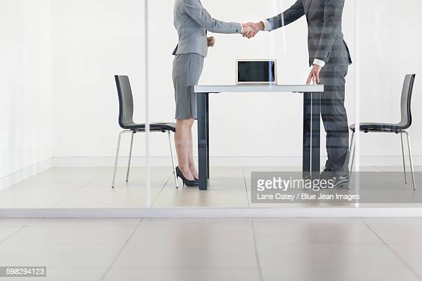Business person shaking hands in meeting room