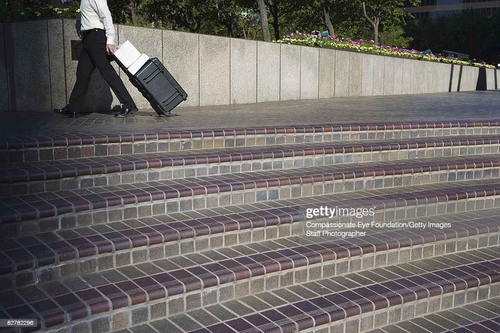 Business person walking by some steps : Stock Photo