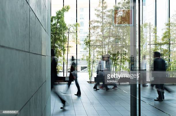 business person walking in a urban building - groene kleuren stockfoto's en -beelden