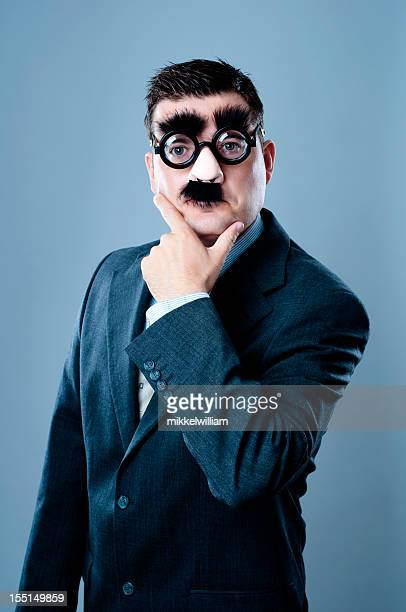 business person with fake nose and mustache - groucho marx stock photos and pictures