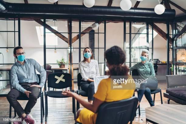 des gens d'affaires lors d'une conférence pendant la pandémie covide-19 - risques liés à une activité photos et images de collection