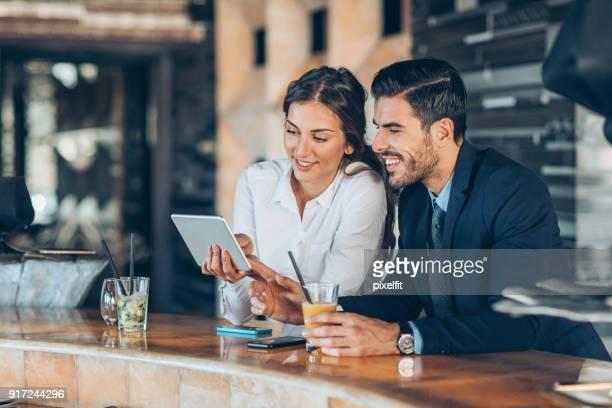 Bedrijfspersonen met digitale Tablet PC- en drankjes in de lobby van het hotel