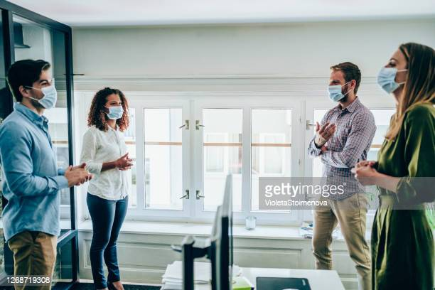 オフィスでの会議で保護フェイスマスクを持つビジネスパーソン。 - 中距離 ストックフォトと画像