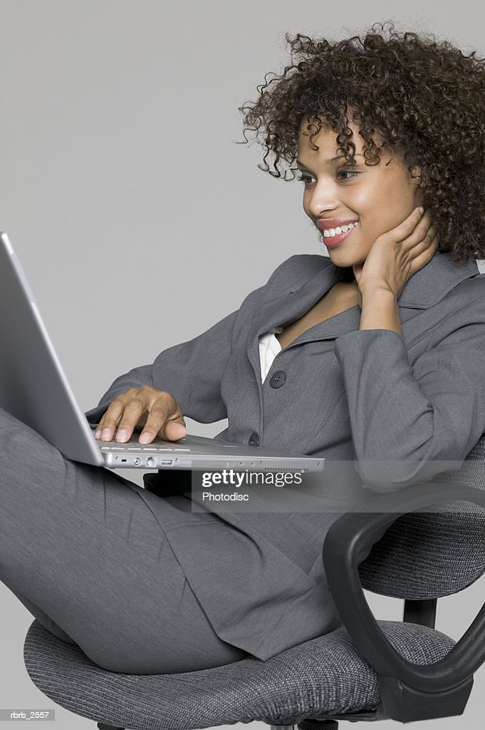 business portrait of a young adult female in a grey suit as she uses her laptop computer : Stock Photo