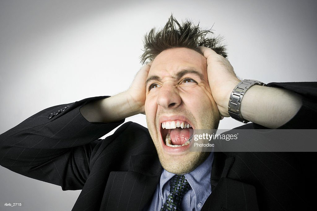 business portrait of a young adult male in a suit as he holds his head and screams : Foto de stock