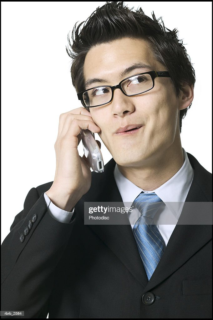 business portrait of a young adult male in a suit as he playfully chats on a cell phone : Foto de stock