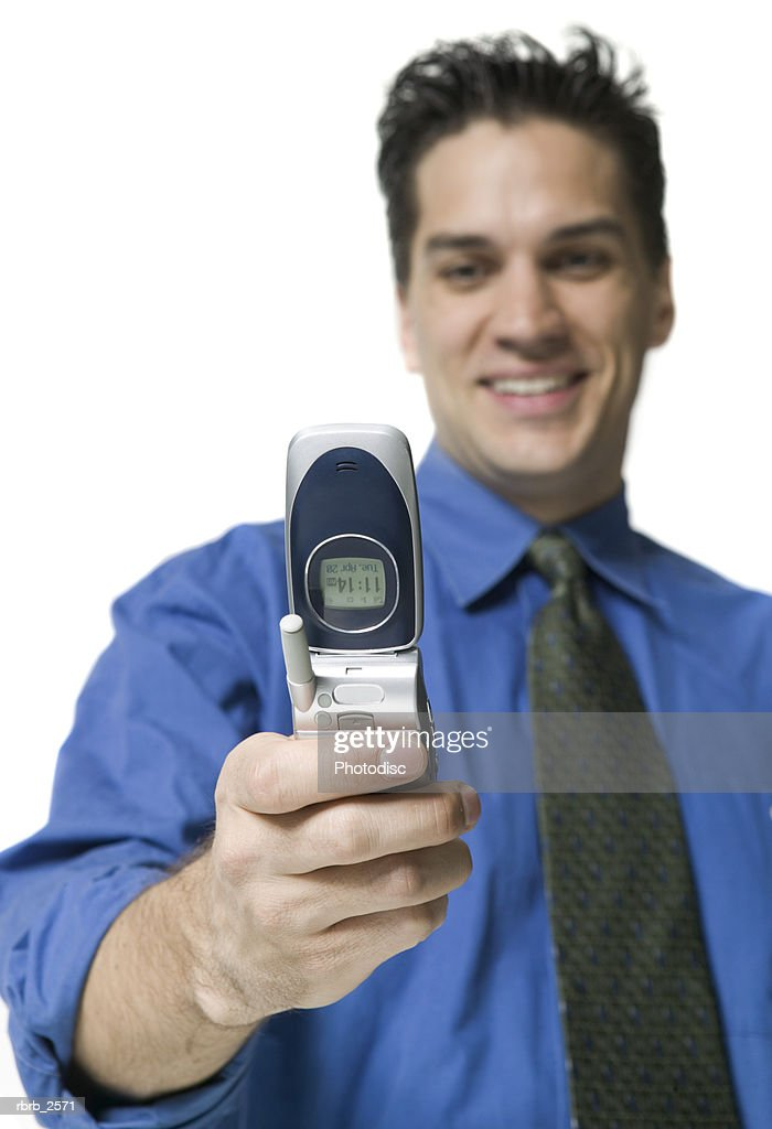 business portrait of a young adult man in a blue shirt as he gets a message off his cell phone : Foto de stock