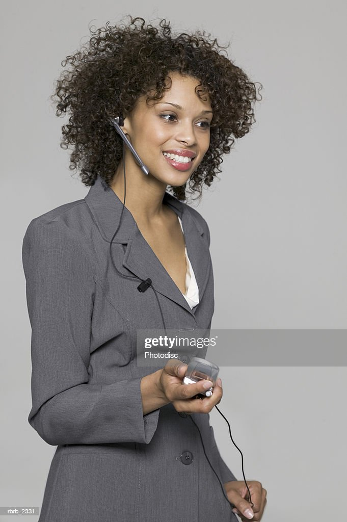 business portrait of a young adult woman in a grey suit as she chats on a hands free cell phone : Stockfoto