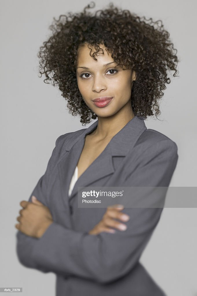 business portrait of a young adult woman in a grey suit as she folds her arms : Foto de stock