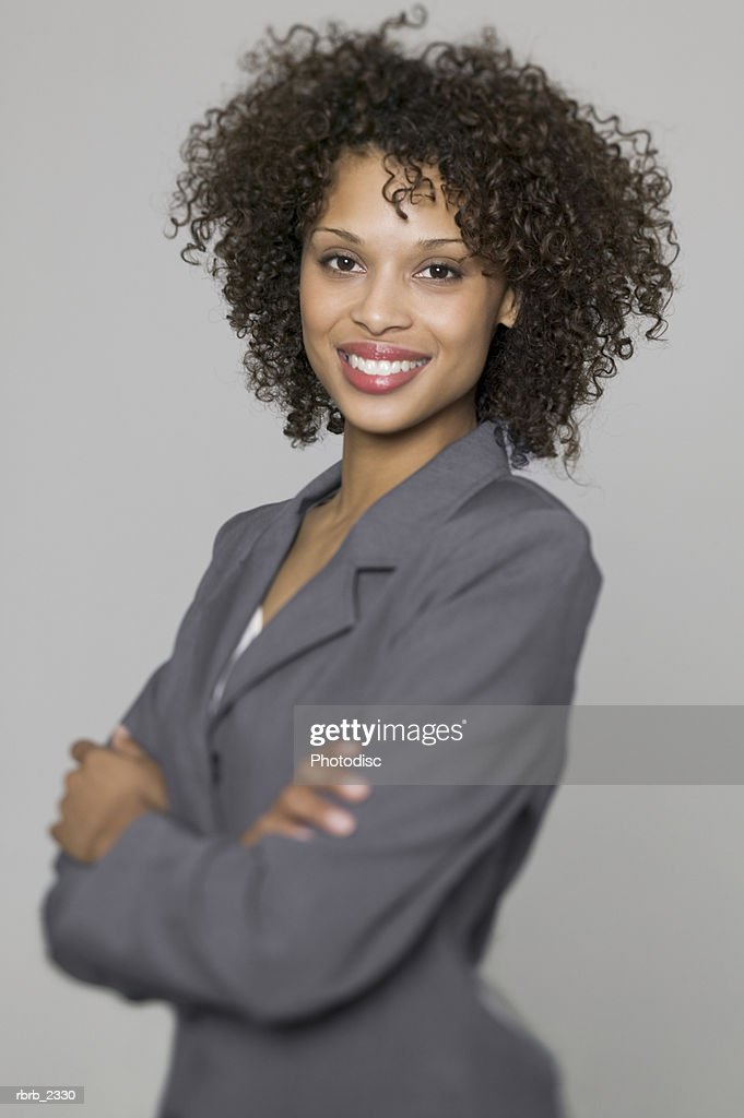 business portrait of a young adult woman in a grey suit as she folds her arms and smiles : Foto de stock