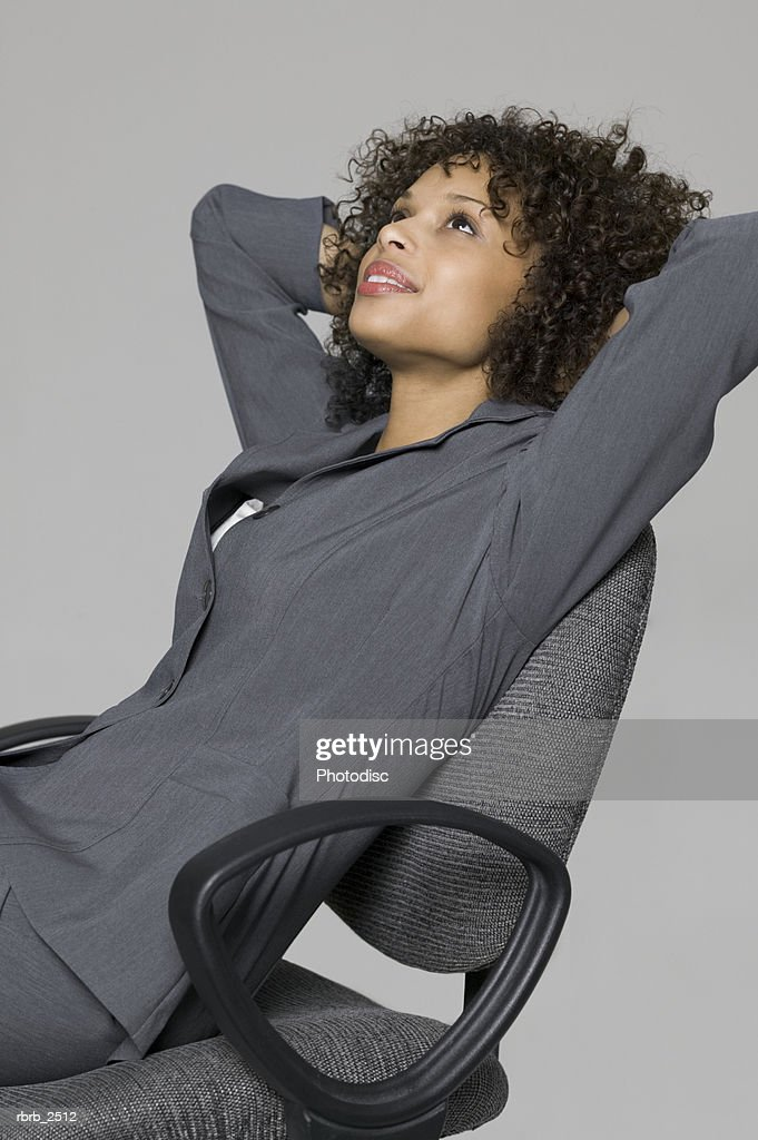 business portrait of a young adult woman in a grey suit as she leans back in her chair : Foto de stock