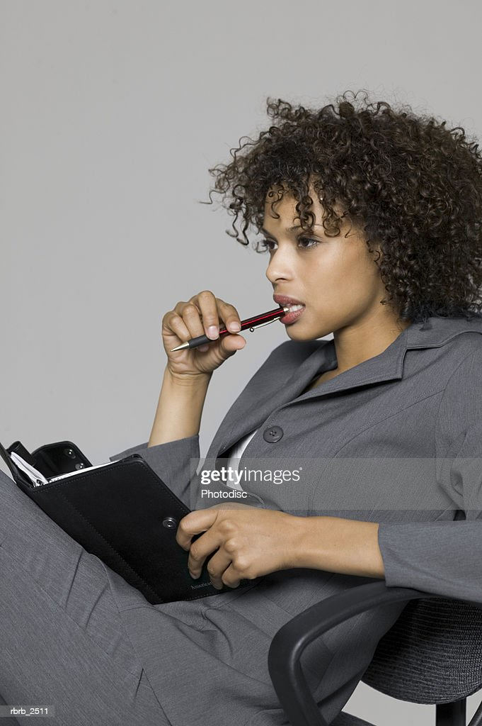 business portrait of a young adult woman in a grey suit as she thinks and writes in her planner : Foto de stock