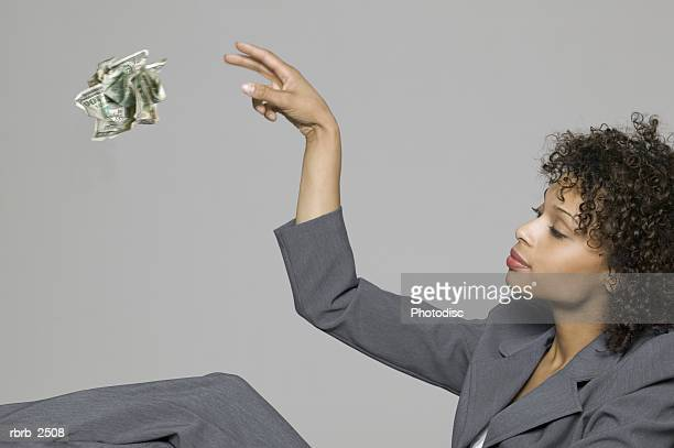 business portrait of a young adult woman in a grey suit as she throws away some cash