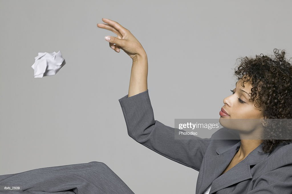 business portrait of a young adult woman in a grey suit as she throws away some trash : Foto de stock