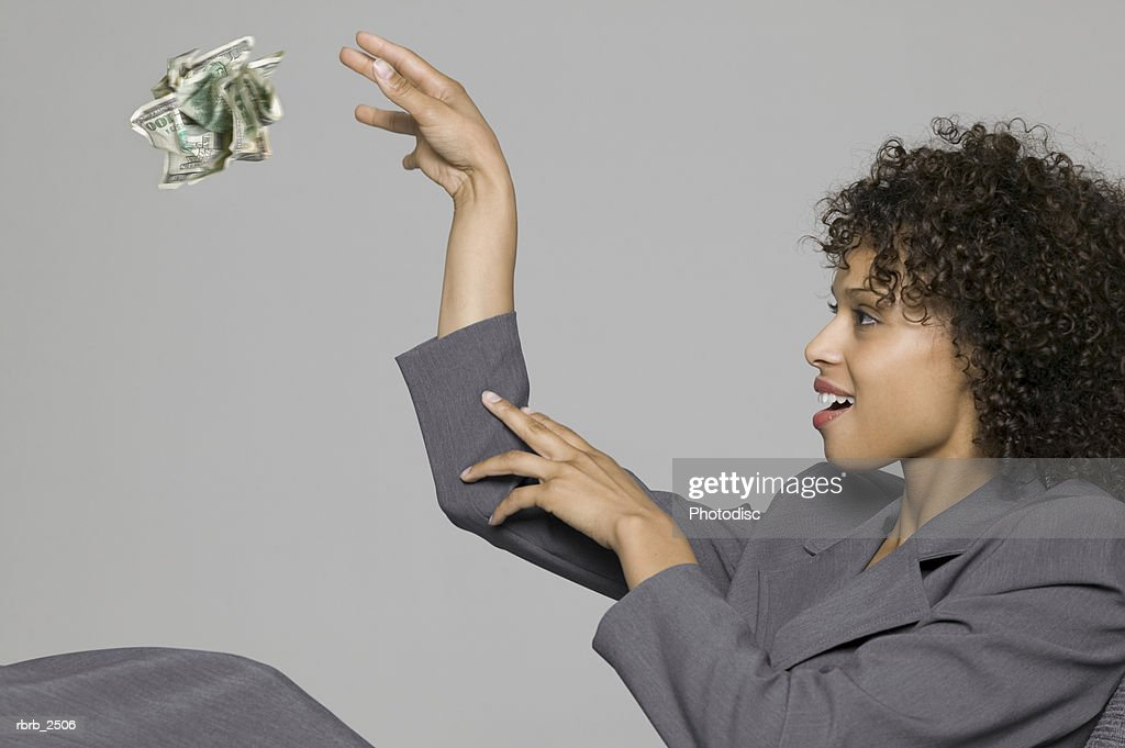 business portrait of a young adult woman in a grey suit as she tosses away a wad of cash : Foto de stock