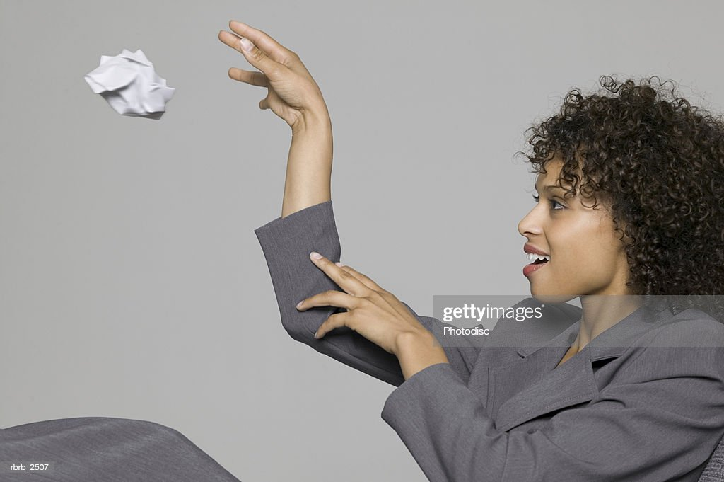 business portrait of a young adult woman in a grey suit as she tosses away a piece of trash : Foto de stock