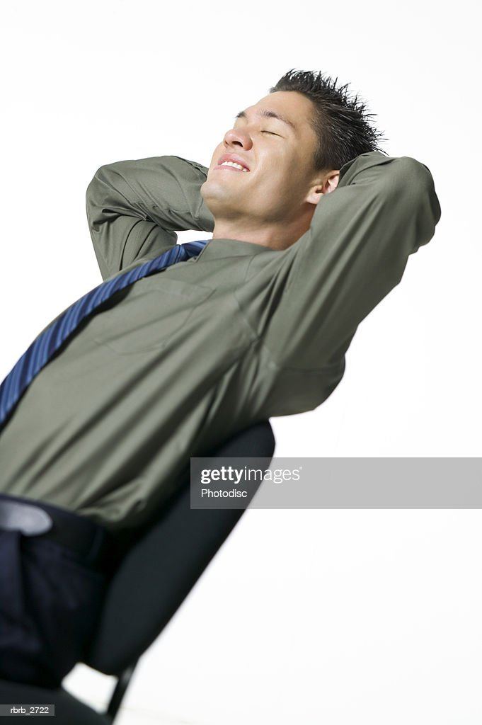 business portrait of an adult male in a green shirt as he leans back in his chair and smiles : Foto de stock