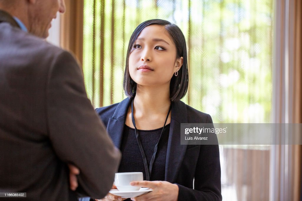 Business professional discussing at break in seminar : Stock Photo