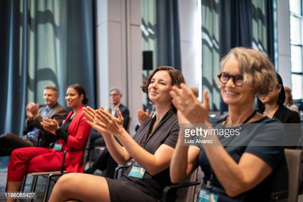business professionals applauding during conference - publikum stock-fotos und bilder