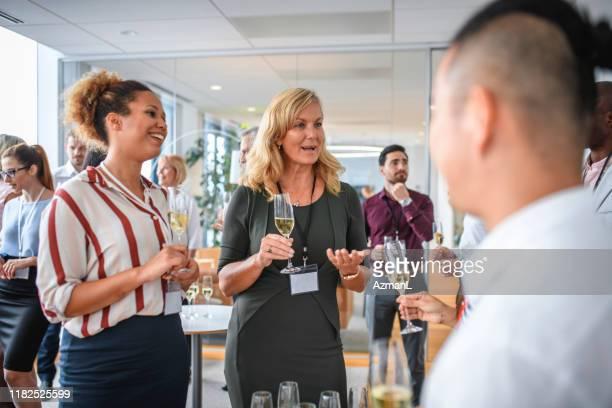 business professionals attending new business launch party - launch event imagens e fotografias de stock