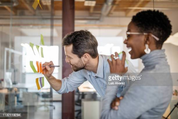 business professionals brainstorming using adhesive notes - human relationship stock pictures, royalty-free photos & images