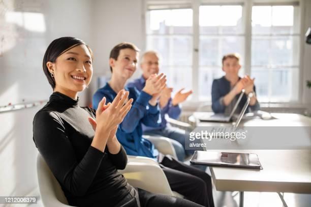 会議で手を叩くビジネスの専門家 - セールストーク ストックフォトと画像