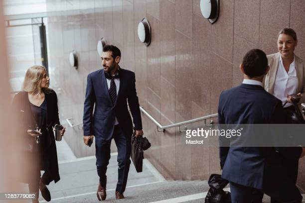 business professionals climbing steps while coworkers standing in city - 30 39 years stock pictures, royalty-free photos & images