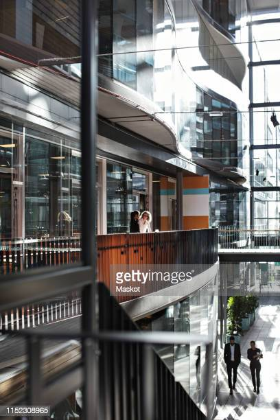 business professionals discussing in atrium at modern office - gothenburg stock pictures, royalty-free photos & images