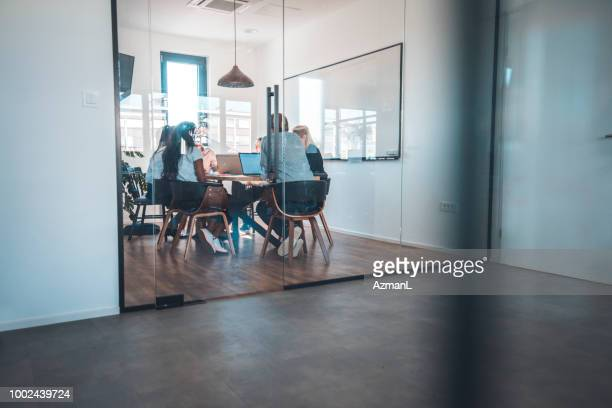 business professionals discussing in board room - photographed through window stock pictures, royalty-free photos & images