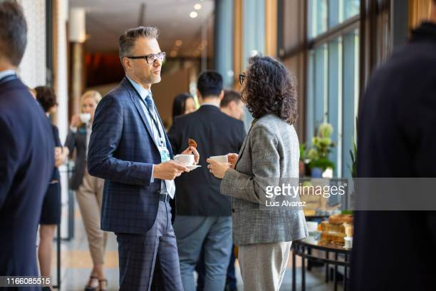 business professionals during a coffee break in auditorium - event stock pictures, royalty-free photos & images