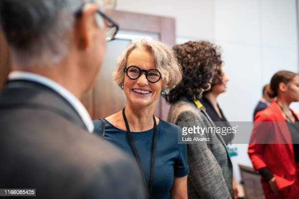 business professionals having a casual chat before a launch event - attending stock pictures, royalty-free photos & images