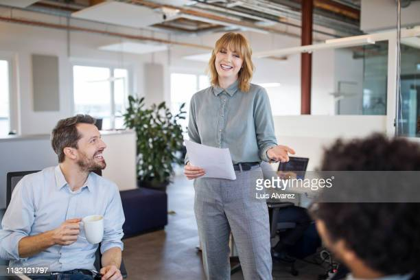 business professionals having casual discussion in office - 女性管理職 ストックフォトと画像