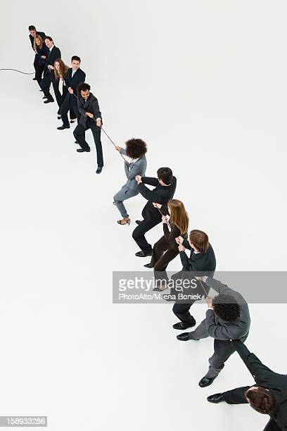 Business professionals in tug-of-war match