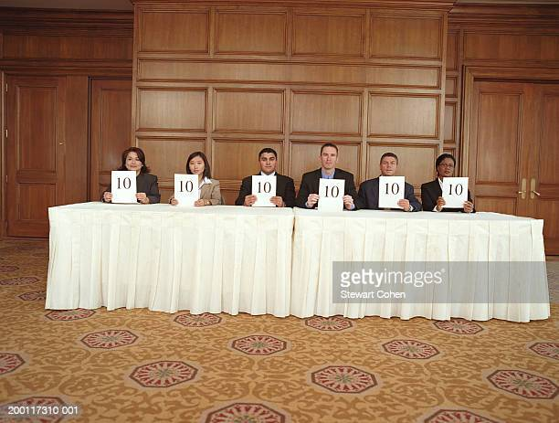 Business professionals sitting at table, holding score cards